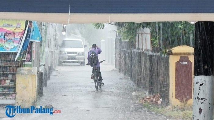 Ilustrasi: Seorang remaja mengayuh sepeda saat hujan turun di Jalan Damar, Kota Padang, Jumat (26/2/2021).