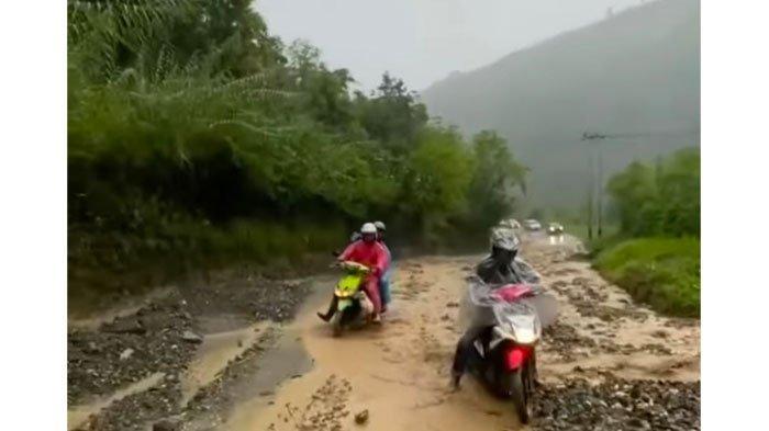 Pengendara sepeda motor mencoba melewati jalan yang tertimbun material longsor bukit di Kawasan Aia Dingin Lembah Gumanti Kabupaten Solok Senin (10/5/2021).