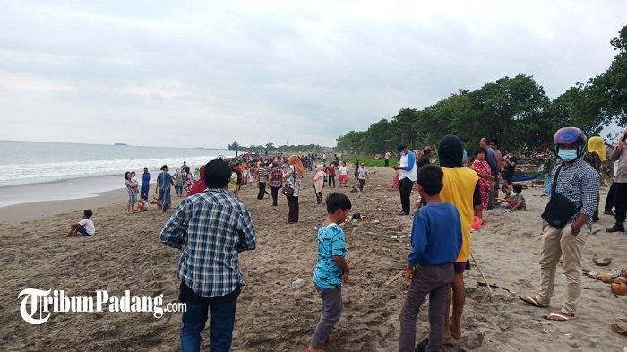 Masyarakat ramai di lokasi seorang anak dilaporkan hanyut di Pantai Lolong belakang Taman Makam Pahlawan, Kelurahan Ulak Karang Kecamatan Padang Barat, Kota Padang, Sumatera Barat (Sumbar), Jumat (5/3/2021).