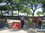 petugas-kepolisian-saat-berjaga-di-kawasan-jalan-masuk-ke-pantai-padang-sabtu-1552021.jpg