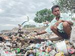 seorang-warga-saat-sedang-memilih-sampah-minuman-kaleng-di-kawasan-pantai-muaro-lasak.jpg