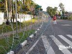 seorang-warga-terpaksa-berjalan-di-aspal-karena-trotoar-ditutupi-kawat-berduri.jpg