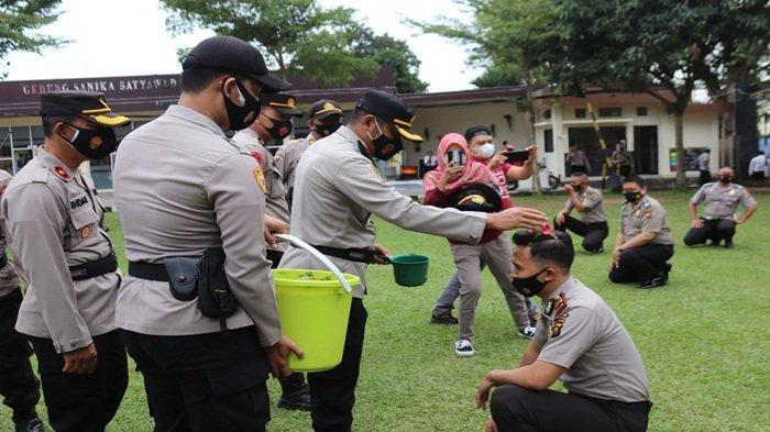 Kapolres Muara Enim AKBP Danny A Sianipar SIk melakukan penyiraman air kembang kepada personil prosesi kenaikan pangkat.