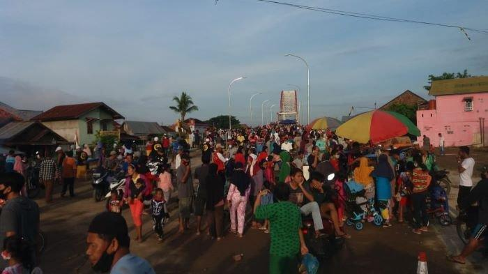 Berkerumun - Warga berkerumun di area jembatan Musi VI, tanpa peduli protokol kesehatan, tidak bermasker dan menjaga jarak.