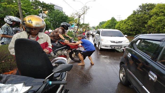 Banjir di Jalan R Sukamto, Sejumlah Warga Dadakan jadi Jasa Angkut Motor ke Median Jalan