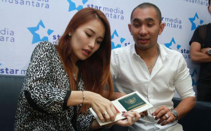 Penyanyi dangdut, Ayu Rosmalina atau Ayu Ting Ting dan suaminya, Henry Baskoro Hendarso alias Enji menunjukkan buku nikah mereka saat menggelar jumpa pers di Studio 6 RCTI, Kebon Jeruk, Jakarta Barat, Jumat (5/7/2013). Jumpa pers tersebut terkait pernikahan mereka yang terkesan dilakukan secara mendadak dan diam-diam pada Kamis 4 Juli 2013, di rumah Ayu Ting Ting, di Depok, Jawa Barat. Ayu dan Enji tidak memberikan keterangan secara jelas terkait gosip miring yang mengatakan kalau mereka berdua menikah cepat lantaran Ayu sudah hamil duluan.