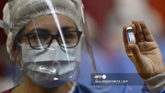 Seorang petugas kesehatan menunjukkan botol vaksin Sputnik V di pusat vaksinasi untuk petugas kesehatan medis, di lapangan basket klub Argentina River Plate, di bawah tribun stadion Monumental, di Buenos Aires pada 2 Februari, 2020.