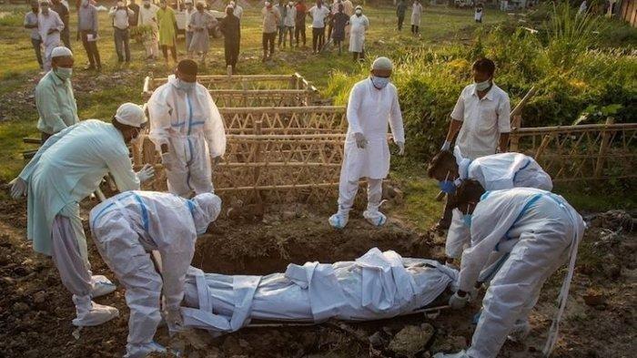Ilustrasi - Petugas memakamkan jenazah pasien covid 19 di India.