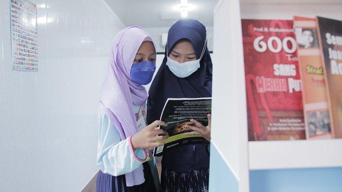 Tampak dua orang remaja putri membaca buka di rumah pintar yang baru diresmikan oleh Direktur Operasi dan Produksi Pusri Filius Yuliandi, yang bekerjasama dengan Komandan Lanal Palembang, Kolonel Laut (P) Filda Malari, dan pemerintahan setempat, Jumat (27/8/2021).