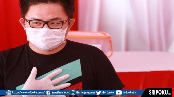 PEJAMKAN MATA SAAT DISUNTIK --- Erik (27), salah satu pedagang Pasar Cinde Palembang yang memiliki tato di tangan kirinya ikut juga divaksin. Awal vaksin, saat petugas kesehatan menyuntikkan vaksin COVID-19, pemuda ini meringis memalingkan muka dan pejamkan matanya. Erik yang berusia 27 tahun ini mengakui takut dengan jarum suntik, namun demi kesehatan dia bersama 252 pedagang Pasar Cinde Palembang menjalani vaksin Covid-19 dosis pertama, di halaman Bank Mandiri Jalan Jendral Sudirman Palembang, Rabu (3/3/2021). SRIPOKU.COM/SYAHRUL