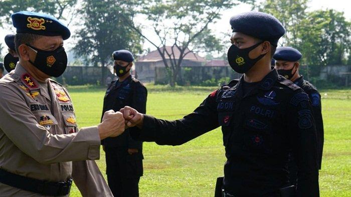 Kapolda Sumsel Irjen Pol Prof Dr Eko Indra Heri S MM salam tos dengan salah satu personil Brimob BKO ketika pelepasan untuk penanganan karhutla, dilapangan Sepak Bola Pakri, Jumat (9/7/2021).