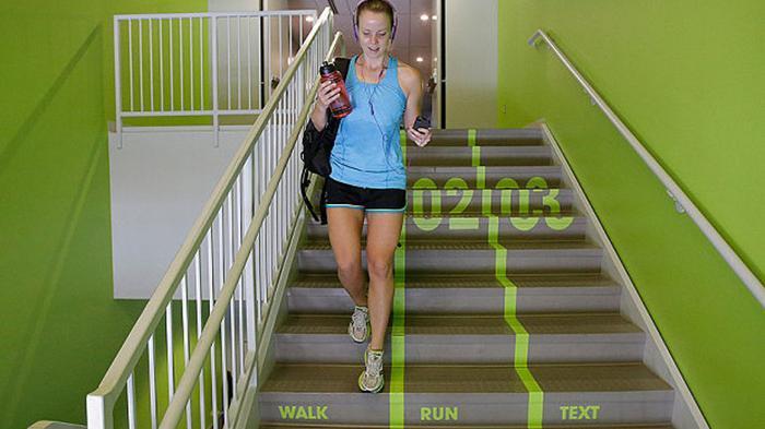 Jody Nelson, mahasiswa Utah Valley University menuruni tangga bergaris hijau cerah yang membagi tiga jalur untuk pejalan kaki, berlari dan penulis SMS sambil berjalan.