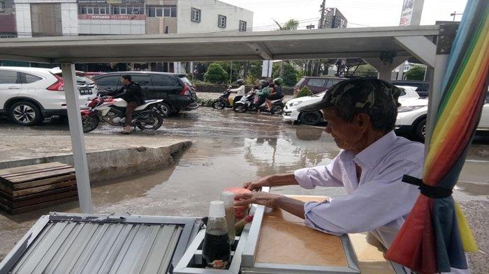 Kakek 72 Tahun Pedagang Pempek Panggang Ini tak Henti Memandang Banjir di Jl R Sukamto Palembang