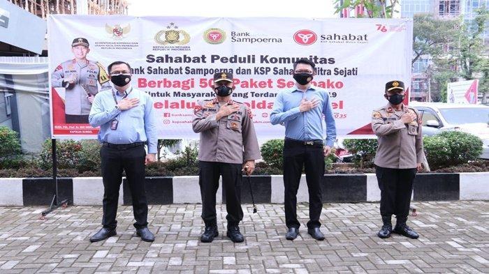 Kapolda Sumsel, Irjen Pol Prof Dr Eko Indra Heri S MM didampingi Wakapolda Sumsel Brigjen Pol Rudi Setiawan SIk SH MH dan pimpinan Bank Sahabat Sampoerna dan KSP Sahabat Mitra Sejati Palembang, berfoto bersama, usai menyerahkan bantuan paket sembako,di Lobby Gedung Promoter Mapolda Sumsel, Senin (23/8/2021).