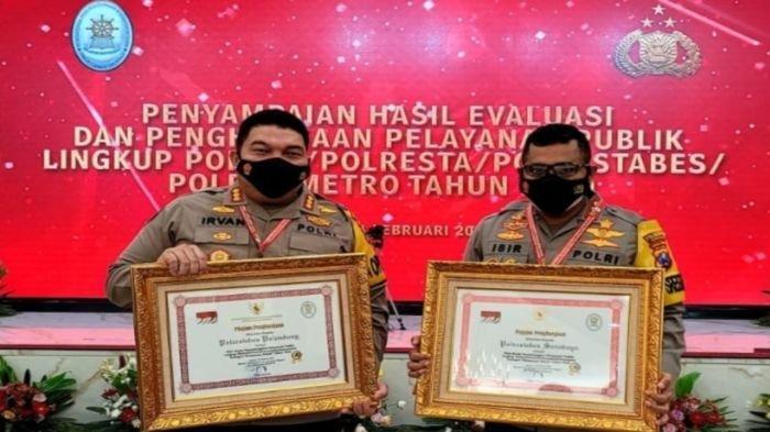 Kapolrestabes Palembang Kombes Pol Irvan Prawira (kiri) memegang penghargaan pelayanan publik dalam kategori pelayanan prima, Selasa (16/2/2021).