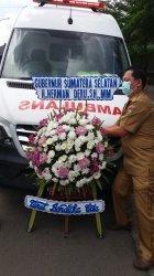 Petugas mempersiapkan pemasangan karangan bunga duka cita dari Gubernur Sumsel Herman Deru, di mobil jenazah yang akan menggiring jenazah Bupati OKU Kuryana Azis di depan RS RK Charitas, Senin (8/3/2021).