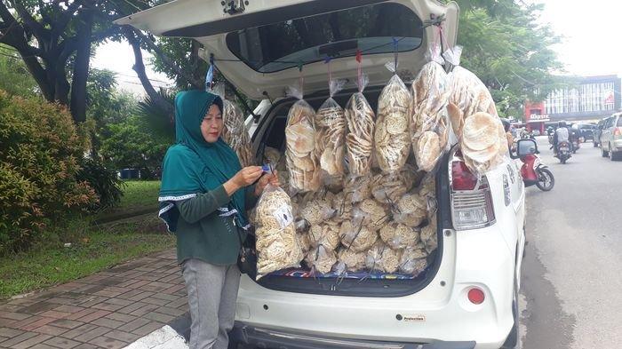 Yati (59) menjajakan kerupuk-kemplang menggunakan Honda Brio di pinggir jalan kawasan Balap Sepeda Kampus Palembang, Jumat (16/2/2019).