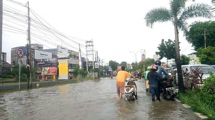 Sejumlah Warga Mengais Rezeki dari Banjir di Jalanan Palembang