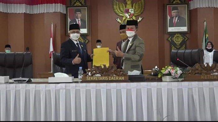 Pj Sekretaris Daerah (Sekda) Muhsin Abdullah dan Ketua DPRD Ogan Ilir (OI) Suharto menunjukan ke tujuh pandangan fraksi yang ditandatangani.