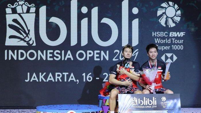 Pasangan ganda putra Indonesia, Marcus Fernaldi Gideon/Kevin Sanjaya Sukamuljo, berpose di podium juara Indonesia Open 2019 di Istora Senayan, Jakarta, Minggu (21/7/2019)