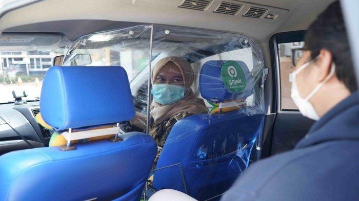 Seorang wanita sebagai driver GoCar kelihatan tampak ramah kepada salah satu penumpang yang hendak diantar ke tempat tujuan.