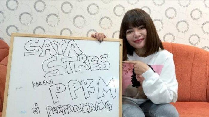 Dinar Candy dengan papan protesnya PPKM Diperpanjang.