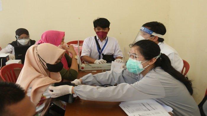 Tampak warga melakukan pemeriksaan tensi darah sebelum disuntik vaksin oleh para bidan, perawat dan dokter pada acara peduli vaksin oleh dinas Kesehatan Kota Palembang bersama Pramuka Kota Palembang, di Bumi Perkemahan Cadika KM 5,5 Palembang, Rabu (29/9/2021).