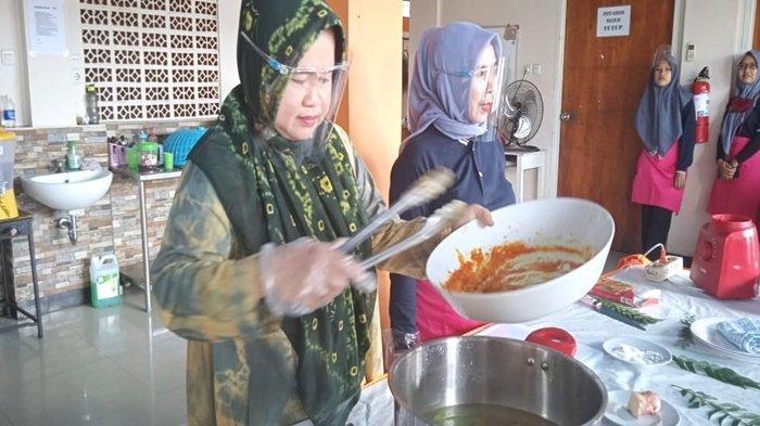 Rini Novita saat memasak pindang patin tempoyak.