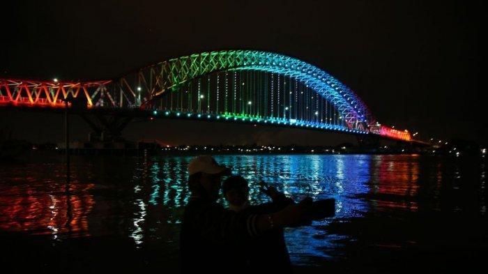 BERITA FOTO : Selfie Warga di Jembatan Musi VI Dilatari Lampu Warna Warni pada Malam Hari