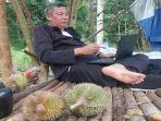 seorang-warga-menikmati-sensasi-liburan-di-kebun-durian-bersama-keluarga-di-oku.jpg