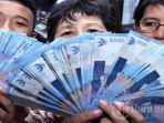 warga-ibukota-memperlihatkan-uang-rupiah-nominal-rp-50-ribu.jpg