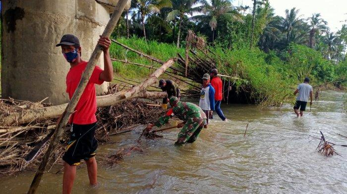Antisipasi Banjir, Babinsa Koramil 03 Batui bersama Warga Bersihkan Batang Pohon di Sungai Moilong
