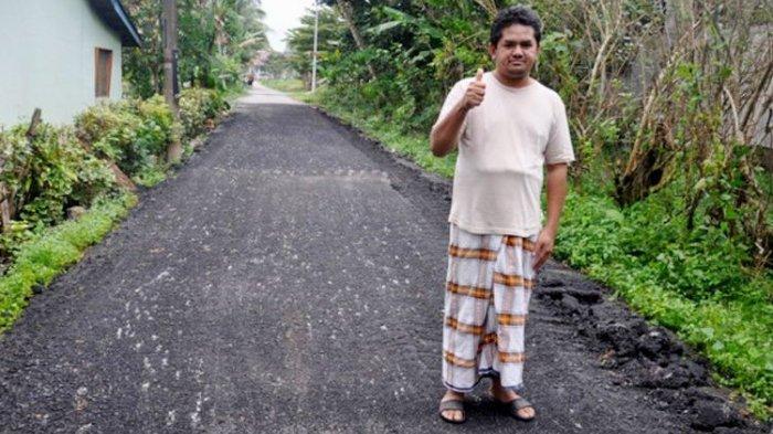 Nor Muhamad Roslam Harun (40) warga Kampung Padang Luas, Jerteh, Malaysia, yang membuat 11 polisi tidur di jalan samping rumahnya, berpose setelah menghancurkan semua polisi tidur itu usai dikomplain warga.