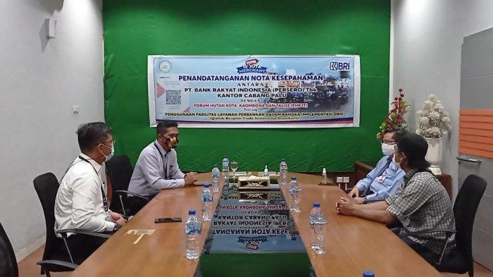 Penandatanganan nota kesepakatan antara Forum Hutan Kota Kaombona Talise (HK2T) dengan BRI Cabang Palu tentang implementasi QRIS di Kantor BRI Cabang Palu, Jl Dr Moh Hatta, Palu Timur, Kota Palu, Sulawesi Tengah, Senin (26/7/2021).