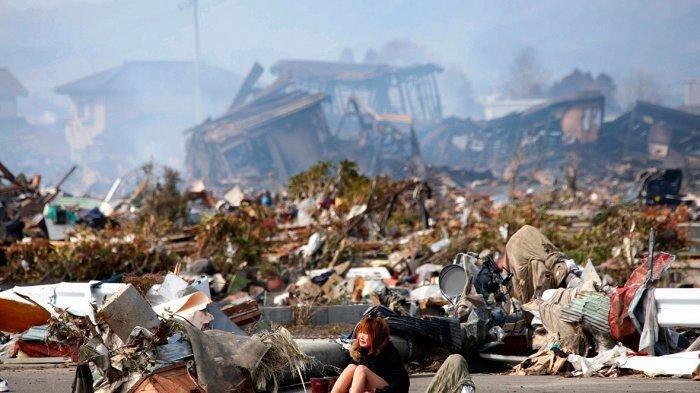 Seorang wanita menangis sambil duduk di jalan tengah kota yang hancur.