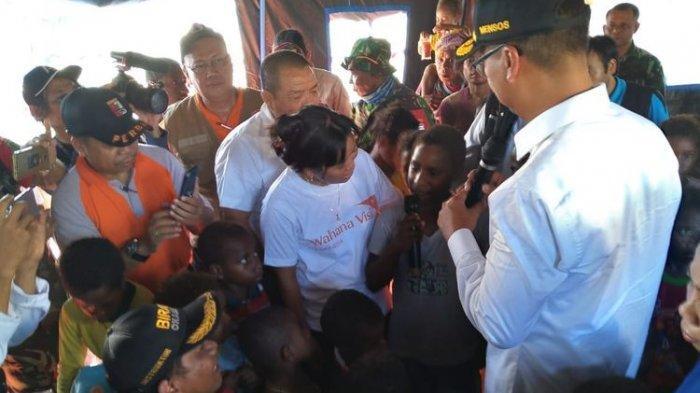 Menteri Sosial Agus Gumiwang Kartasasmita (mengenakan topi) sedang mendengar harapan dari Rini Enundi, salah satu anak-anak yang terdampak banjir bandang yang sedang mengungsi di Stadion Barnabas Youwe, Kabupaten Jayapura, Papua, Rabu (27/3/2019).