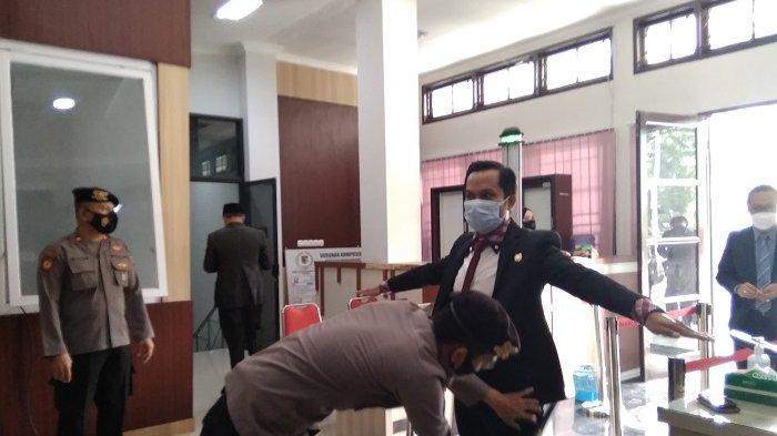 Polisi memeriksa salah seorang anggota DPRD Palu saat hendak masuk ke ruang sidang, Minggu (21/2/2021).
