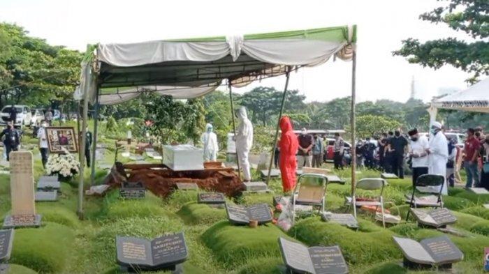 Prosesi pemakaman Rina Gunawan, tampak Teddy Syach dan anaknya menggunakan APD