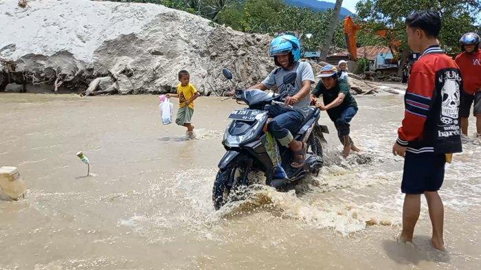 Sejumlah masyarakat khususnya pemuda di Desa Rogo Kecamatan Dolo Selatan Kabupaten Sigi membantu pengendara R2 dan R4 untuk melintasi luapan air di Desa Rogo, Senin (6/9/2021) siang.