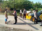 polisi-bersama-warga-memperbaikijalan-rusak-di-jalan-trans-sulawesi-kelurahan.jpg
