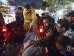 relawan-dan-staf-medis-menurunkan-mayat-dari-truk-pickup.jpg