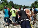 warga-mengevakuasi-korban-tewas-di-tepi-sungai-batui.jpg
