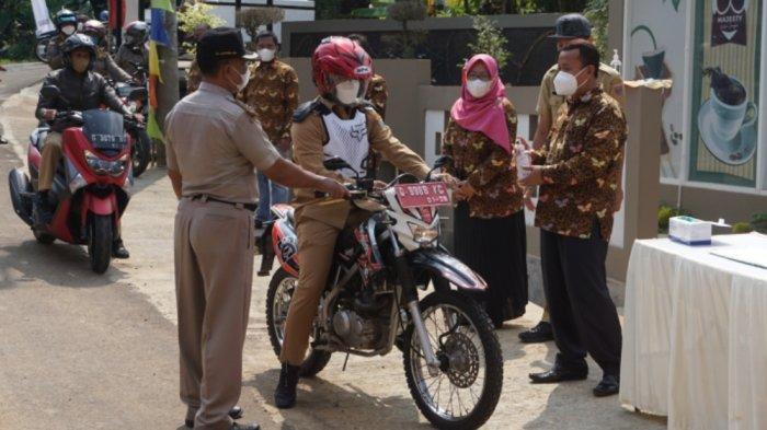 Bupati Batang Wihaji mengendarai sepeda motor memberikan ucapan selamat saat menghadiri acara khitanan drive thru, Selasa (3/8/2021).