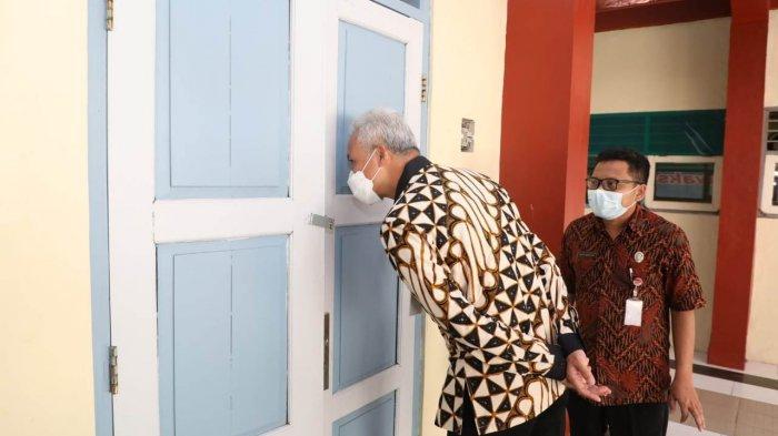 Gubernur Jawa Tengah, Ganjar Pranowo, mengintip ruang kelas saat meninjau pelaksanaan PTM di SMKN 1 Tengaran, Kabupaten Semarang, Jumat (24/9/2021).