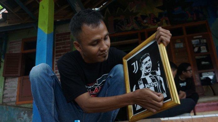 Maliki menunjukkan satu di antara sekian lukisan dari lakban hitam pesanan customer di rumahnya di Desa Kemiri Barat, Kecamatan Subah, Minggu (8/8/2021).