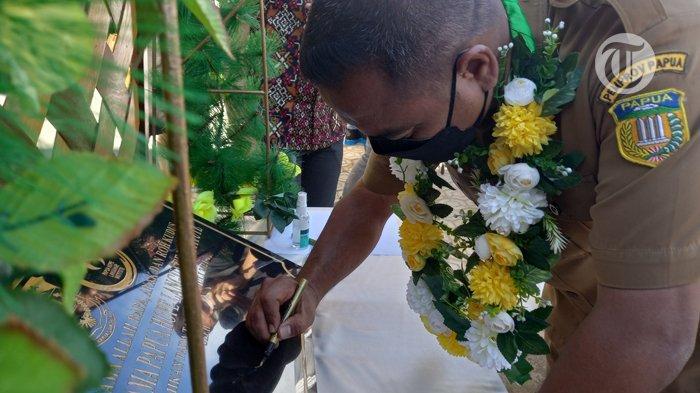 PERESMIAN - Staf Ahli Gubernur Papua Bidang Penanganan Otonomi Khusus, Triwarno Purnomo saat menandatangani prasasti peresmia  gedung asrama Hope Language Institute (PHLI).