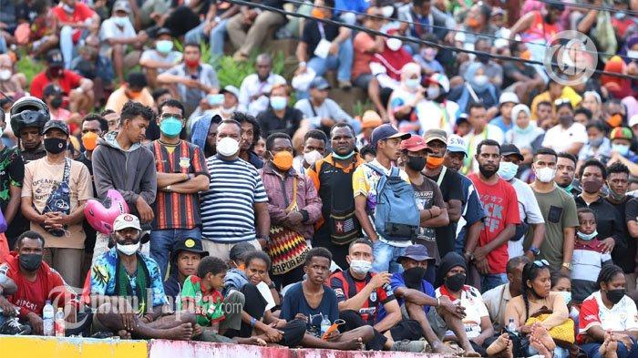 Sejumlah penonton terlihat memadati bangku penonton saat laga final sepakbola putra antara Papua vs Aceh di Stadion Mandala, Jayapura, Papua, Kamis (14/10/2021). Laga antara Papua vs Aceh dimenangkan oleh Papua dengan skor 2-0 yang membuat Papua meraih medali emas.