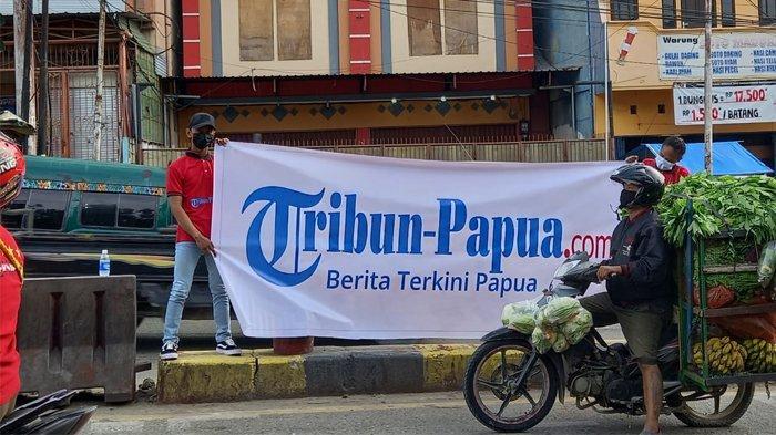 Sales Promotion Girl (SPG) sedang membentangkan baliho Tribun-Papua.com di Lampu Merah Abepura, Kota Jayapura, Provinsi Papua, Jumat (18/6/2021).