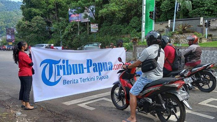 Sales Promotion Girl (SPG) sedang membentangkan baliho Tribun-Papua.com di Lampu Merah Dok II, Kota Jayapura, Provinsi Papua, Jumat (18/6/2021).