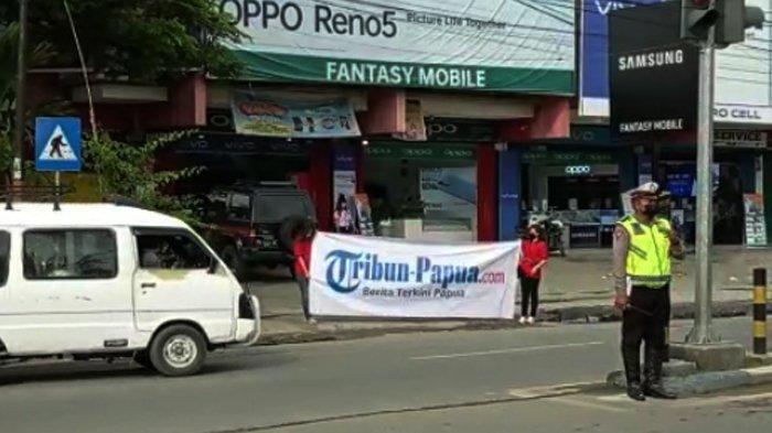 Sales Promotion Girl (SPG) sedang membentangkan baliho Tribun-Papua.com di Lampu Merah Sentani, Kabupaten Jayapura, Provinsi Papua, Jumat (18/6/2021).
